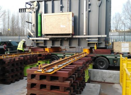Unloading and positioning a transformer with a jacking and skidding system